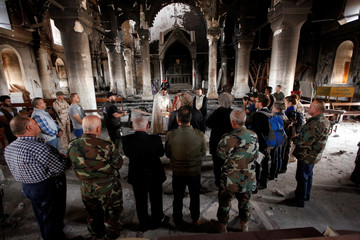 Iraqi priests hold the first mass at the Grand Immaculate Church since it was recaptured from Islamic State in Qaraqosh