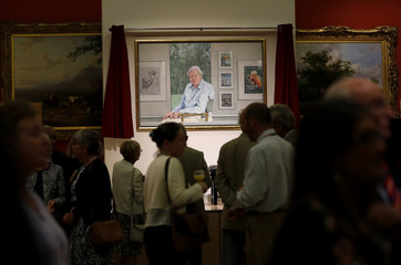 Visitors view a portrait of David Attenborough by Bryan Organ to mark his 90th birthday at New Walk Museum and Art Gallery in Leicester