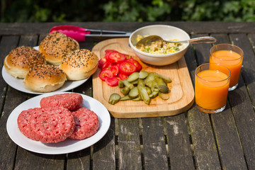 Barbecue, BBQ in the garden. Ingredients. Fresh burger with beef on wooden table.