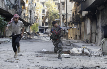 Mohammad, 13 year-old fighter from Free Syrian Army, aims his weapon as he runs from snipers loyal to the Syrian regime in Aleppo's Bustan al-Basha district