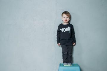 Portrait of standing little boy studio shoton gray background