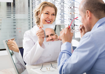 Mature doctor and male customer choosing glasses