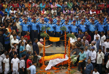 Nepali police officers salute as people watch the son of Senior Superintendent of Police (SSP) Laxman Neupane cremate his father, who was killed in Monday's protest at Tikapur, in Kathmandu