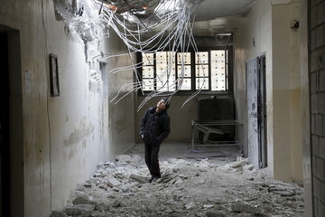 A boy inspects damage inside his school, due to what activists said was an air strike carried out yesterday by the Russian air force in Injara town, Aleppo countryside, Syria