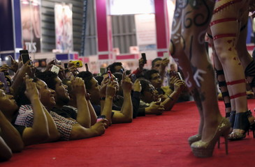 """Visitors take pictures with their cell phones of exotic dancers at the """"Sex and Entertainment Expo"""" adult exhibition at the Palacio de los Deportes in Mexico City"""