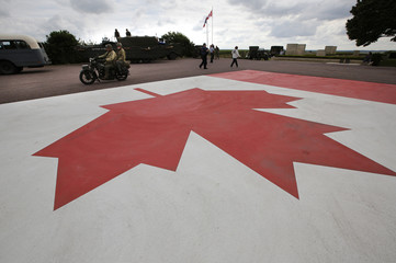 World War Two re-enactors ride a vintage motorcycle past a Canadian flag painted on the parking lot at the Canadian military cemetery in Beny-sur-Mer