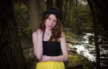 Cute young girl in a black hat. Red-haired girl. Yellow skirt. Girl In the woods