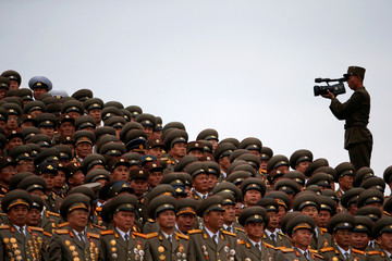 A solider films military officers following a mass dance performance in the capital's main ceremonial square, a day after the ruling Workers' Party of Korea party wrapped up its first congress in 36 years, in Pyongyang