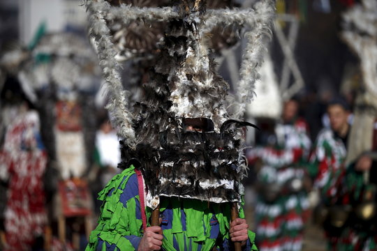 Participant dressed in traditional costume holds his mask during the International Festival of the Masquerade Games in the town of Pernik