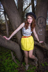 Cute young girl in a black hat. Red-haired girl. Yellow skirt. Girl In the woods.
