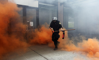 A police officer in riot gear emerges from the colored smoke in front of destroyed storefronts during May Day demonstrations