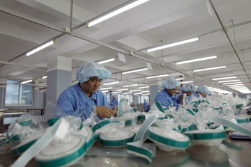 ForTunique employees work to make hospital gowns and other products at a production line in a factory in Guangzhou