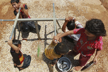 Syrian refugee children play with water on a hot day at the Al Zaatri refugee camp in the Jordanian city of Mafraq, near the border with Syria