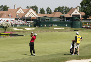 Tiger Woods of the U.S. hits from the 18th fairway with the clubhouse in the background during the first round of the 93rd PGA Championship golf tournament at the Atlanta Athletic Club in Johns Creek