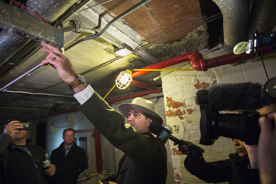 Superintendent of the Statue of Liberty and Ellis Island National Parks Luchsinger shows reporters how high the water flooded the basement of the Ellis Island immigration museum building in New York