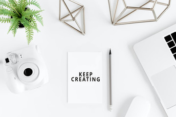 Top view of keep creating motivational quote and instant camera at workplace