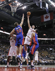 Toronto Raptors' Valanciunas goes to the basket against Detroit Pistons' Kravtsov and Daye during the second half of their NBA preseason basketball game in Toronto