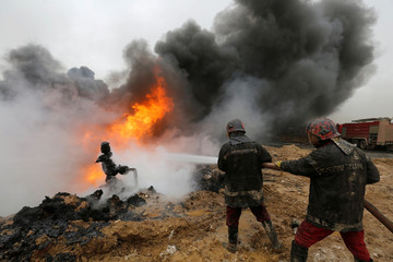 Fiirefighters put out a fire at oil wells, which were set ablaze by Islamic State militants before they fled the oil-producing region of Qayyara, Iraq