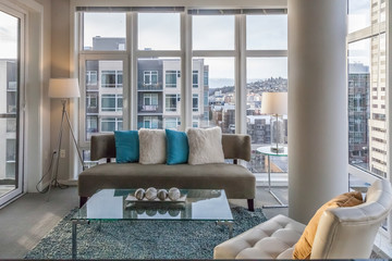 modern living room with teal accents and city view