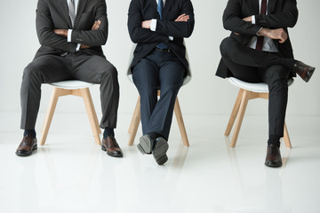 low section of businessmen sitting on chairs isolated on white, businessmen group concept