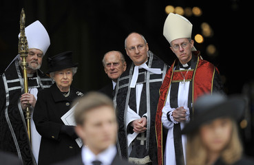 Britain's Queen Elizabeth and Prince Phillip watch as the coffin of former British prime minister Margaret Thatcher is carried outside St Paul's Cathedral after the funeral service, in London