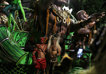 Revellers of the Imperio da Tijuca samba school have their picture taken in front of a float in Rio de Janeiro
