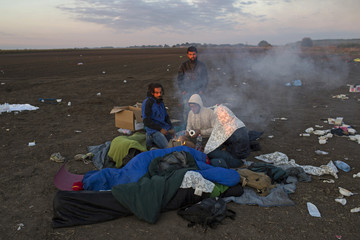 Migrants light a fire to warm themselves as the sun rises at a collection point in the village of Roszke