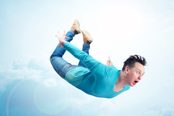 Crazy man in blue shirt and jeans is flying in the sky. Jumper concept