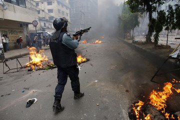 A police officer shoots rubber bullets during a clash with activists of Hefajat-e Islam in Dhaka