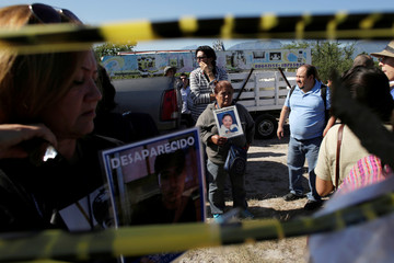 A woman holds a picture of a missing woman during a mass with relatives of missing persons at the site where several bodies were found in mass graves in the municipality of Salinas Victoria Nuevo Leon Mexico