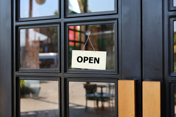 Open sign board hanging on door of cafe.