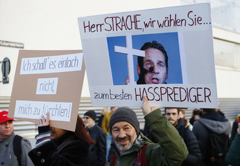 Protesters supporting a refugee home hold up banners during a demonstration in Vienna
