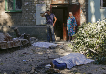 Local residents stand at damaged apartment block near bodies of victims killed by what locals say was recent shelling by Ukrainian forces in Donetsk