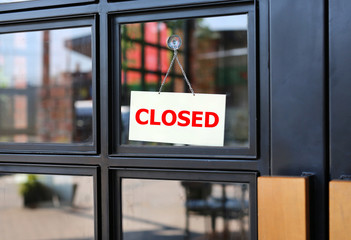 Closed sign board hanging on door of cafe.