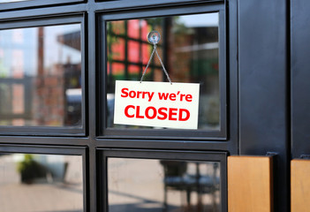 Sorry we're Closed sign board hanging on door of cafe.
