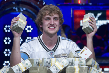 Riess poses with stacks of money after winning the World Series of Poker $10,000 buy-in no-limit Texas Hold 'Em tournament at the Rio Hotel & Casino in Las Vegas, Nevada