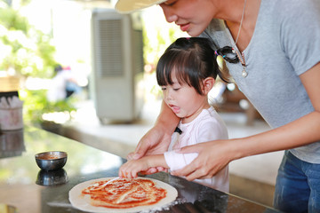 Mother and Cute little girl using Wooden rolling pin on Dough for pizza. Homemade process of preparation pizza.