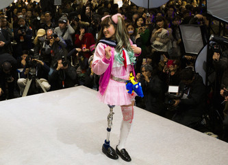 A woman wearing a prosthetic leg participates in a public photo session at the Hasselblad and Profoto booth, during the CP+ camera and imaging equipment trade fair in Yokohama
