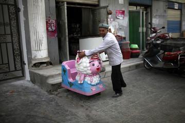 An Uighur man opens his store near a market area in Kashgar, Xinjiang province