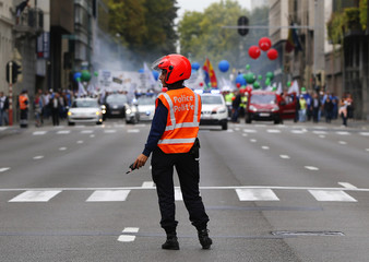 A Belgian police officer controls the traffic in front of a demonstration by police staffs in central Brussels