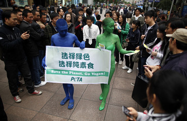 """Two members of PETA hold a banner which reads """"Save the Planet, Go Vegan,"""" as they march along a pedestrian area of Nanjing Road in downtown Shanghai"""