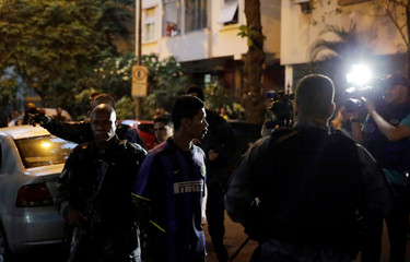 Police officers arrest a suspected drug dealer after a shootout during a police operation at Copacabana neighborhood near the Pavao-Pavaozinho slum in Rio de Janeiro