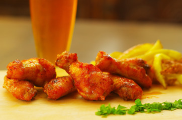 Delicious grilled chicken wings with a glass of beer and french fries behind on wooden board
