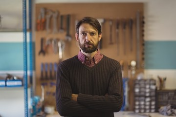 Portrait of serious owner standing at bicycle workshop