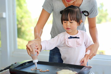 Mother and child making Homemade pancake.