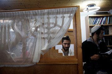 Jewish men pray inside a synagogue in the Jewish settler outpost of Amona in the West Bank
