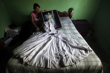 Luz Elena Munoz holds a photograph of her daughter Nancy while sitting next to the dress of Nancy's 15th birthday celebration, in Ciudad Juarez