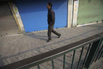 Man walks past closed shops during a shutdown