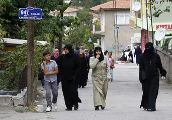 Syrian refugees stroll on a street of a low-income neighborhood in Ankara