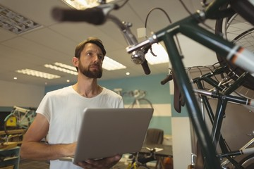 Thoughtful employee holding laptop at bicycle workshop